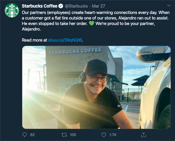 Starbucks employee helping a customer to change the flat tire